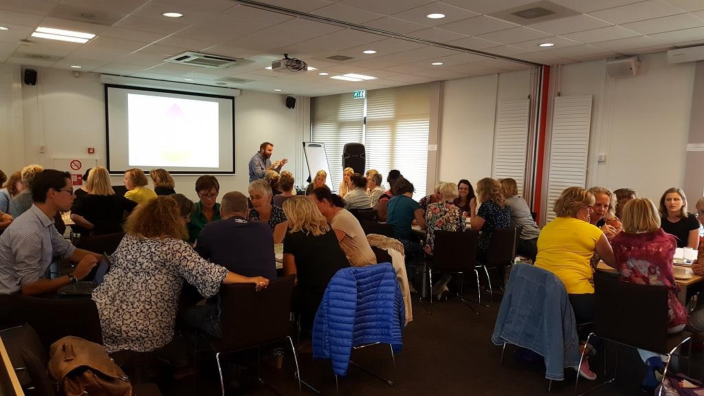 Deelnemers in groepjes bezig aan dagbesteding voor mensen met dementie